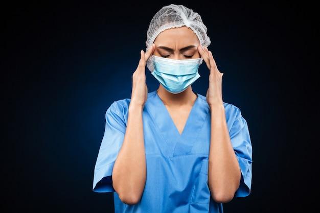 De vermoeide vrouwelijke arts in medisch masker en glb heeft een geïsoleerde hoofdpijn