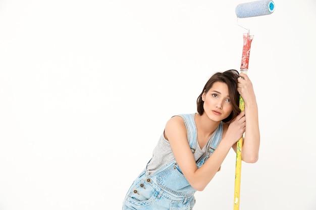 De vermoeide vrouwenbouwer leunt bij het schilderen van schuimrol