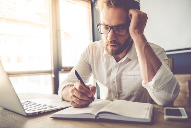 De vermoeide zakenman in oogglazen schrijft in zijn notitieboekje