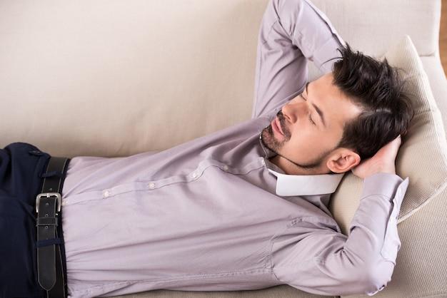 De vermoeide zakenman slaapt op de bank op het kantoor.
