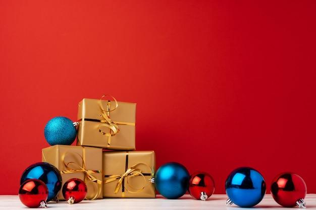 De verpakte dozen van de kerstmisgift tegen rode vooraanzicht als achtergrond