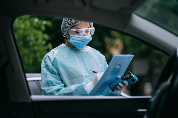 De verpleegster draagt een beschermend pak en masker tijdens de covid19-uitbraak
