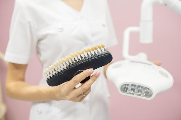 De verpleegster houdt monsters van de kleur van het glazuur van de tanden vast voor demonstratie aan de patiënt tijdens de procedure voor het bleken van hardware in het cosmetologiecentrum