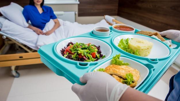 De verpleegster in medische laag houdt een dienblad met ontbijt