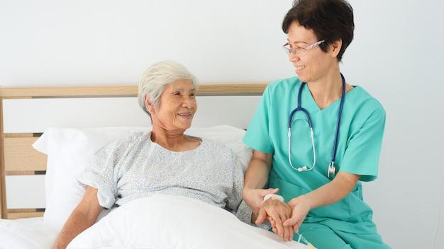 De verpleegster neemt zorg de bejaarde vrouw in het ziekenhuisruimte.