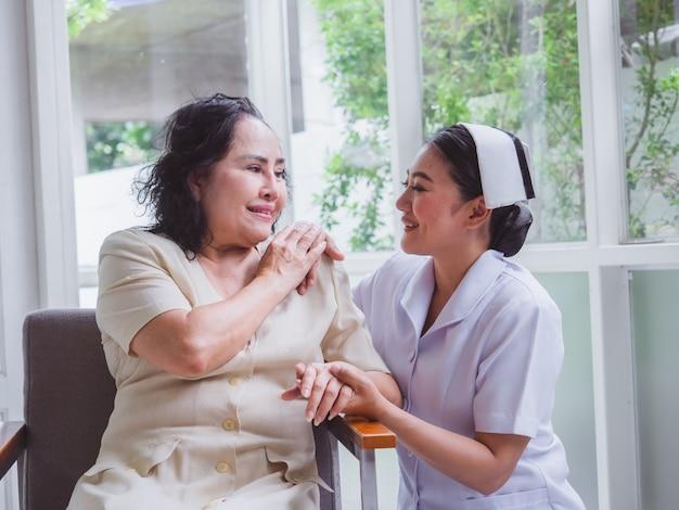 De verpleegster zorgt met geluk voor de ouderen, de verzorger legde zijn hand op de schouders van de oudere vrouw