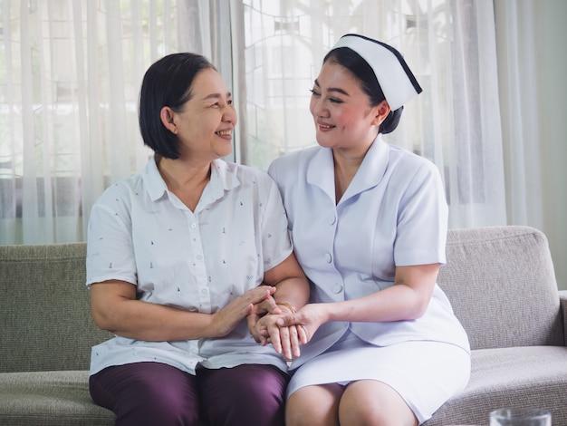 De verpleegster zorgt voor de ouderen met geluk, verzorger legde zijn hand op de hand van de senior vrouw