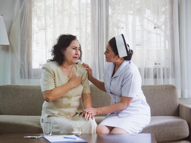 De verpleegster zorgt voor ouderen met geluk, oude vrouwen voelen hartpijn