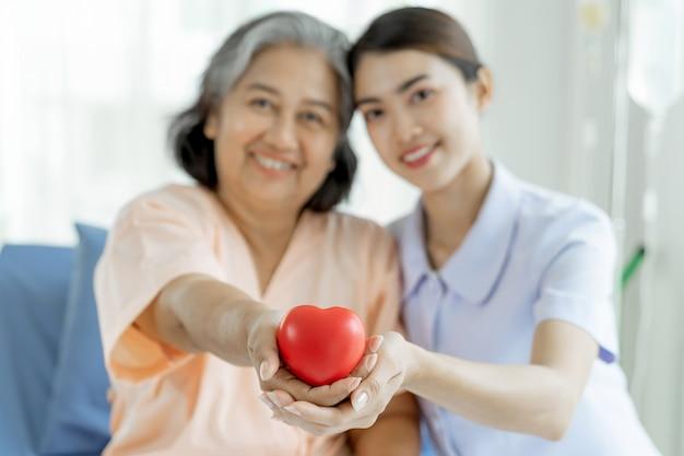 De verpleegsters zijn goed verzorgd voor oudere vrouwen in ziekenhuisbedpatiënten voelen zich gelukkig - medisch en zorgconcept