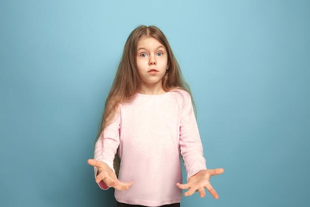 De verrassing. tiener meisje op een blauw. gezichtsuitdrukkingen en mensen emoties concept