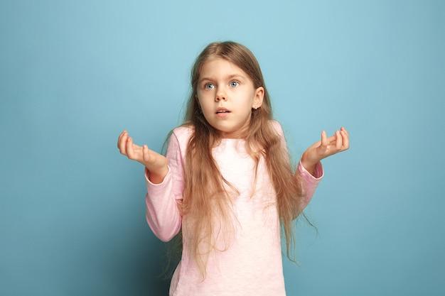 De verrassing, verbijstering, genot. het verraste tienermeisje op een blauwe studioachtergrond. gezichtsuitdrukkingen en mensen emoties concept. trendy kleuren. vooraanzicht. halve lengte portret
