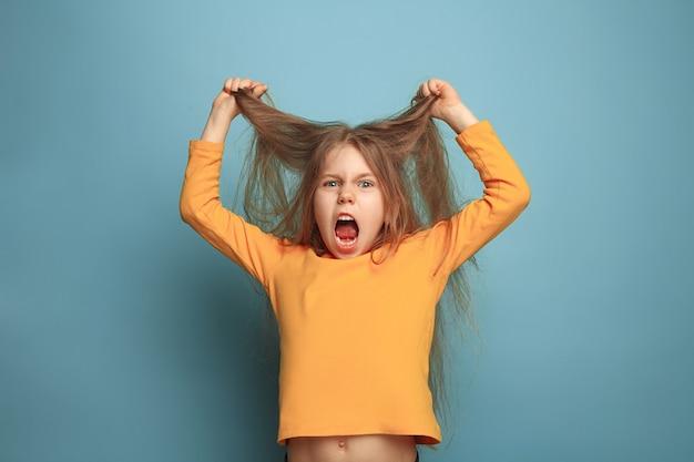 De verrassing, woede. het gillende verrast tienermeisje op een blauwe studioachtergrond. gezichtsuitdrukkingen en mensen emoties concept. trendy kleuren. vooraanzicht. halve lengte portret