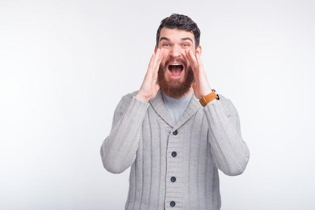 De verraste bebaarde man schuift naar de camera wat goed nieuws.