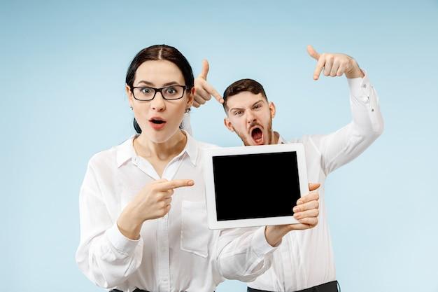 De verraste bedrijfsmens en vrouw die op een blauwe studioachtergrond glimlachen en het lege scherm van laptop of tablet tonen