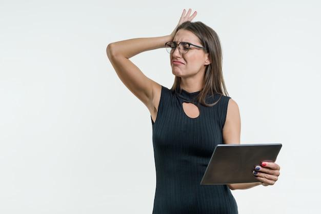 De verraste bedrijfsvrouw met een geschokt gezicht houdt een digitale tablet