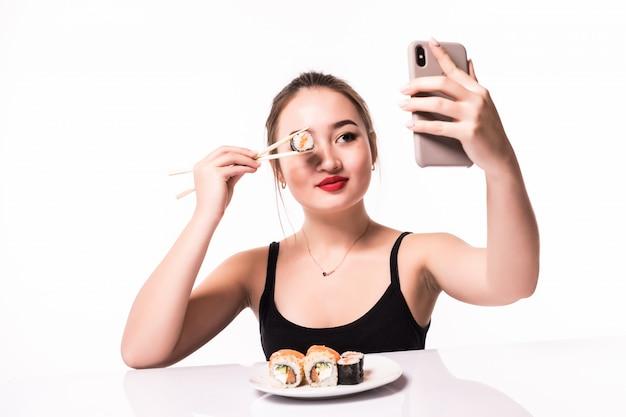 De verraste glimlachende aziatische vrouw behandelt haar oog met sushirol en maakt selfie op haar telefoon