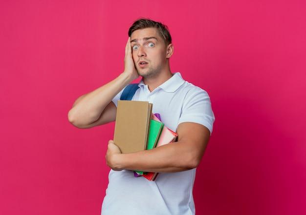 De verraste jonge knappe mannelijke boeken van de studentenholding en hand op gezicht zetten dat op roze wordt geïsoleerd