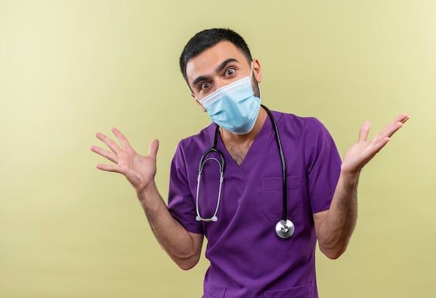De verraste jonge mannelijke arts die purpere chirurgenkleding en het medische masker van de stethoscoop draagt verspreidt handen op geïsoleerde groene muur
