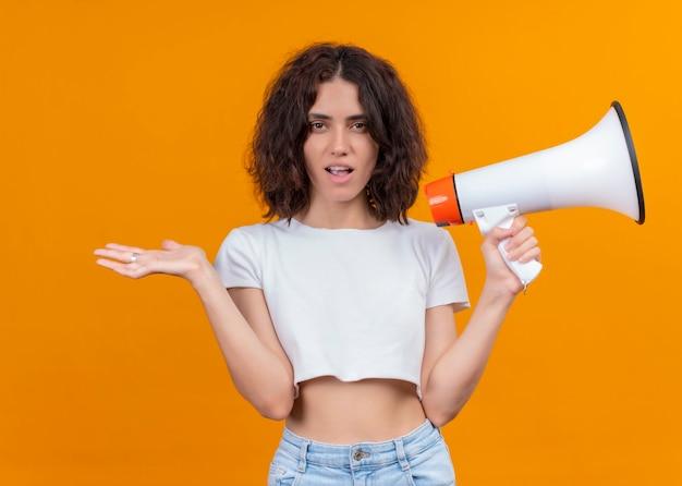 De verraste jonge mooie spreker van de vrouwenholding en het tonen van lege hand op geïsoleerde oranje muur