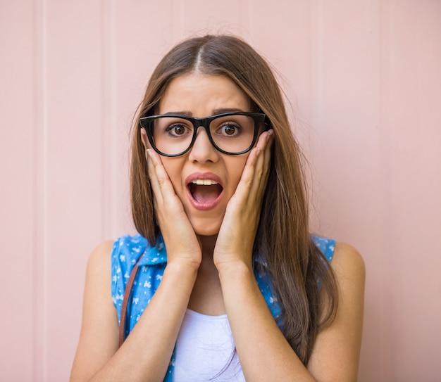 De verraste jonge vrouw in glazen houdt handen op gezicht.