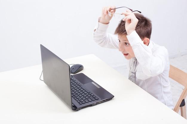 De verraste jongen die zijn laptop computer op witte achtergrond gebruikt.