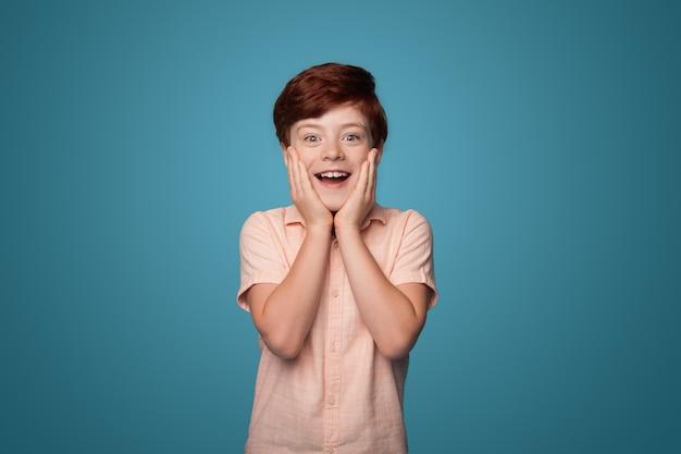 De verraste kaukasische jongen met rood haar dat wangen bedekt met handpalmen glimlacht op een blauwe muur