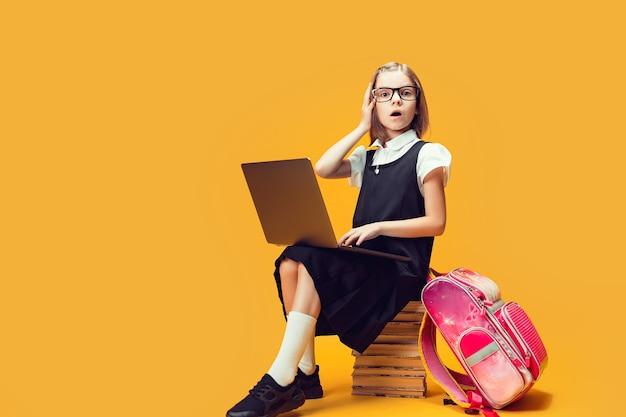 De verraste leerling van de volledige lengte zit op de stapel boeken met een laptop en kijkt naar het onderwijs van de camerakinderen