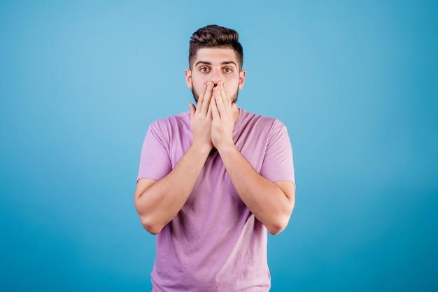 De verraste mens behandelt mond met handen die over blauw worden geïsoleerd