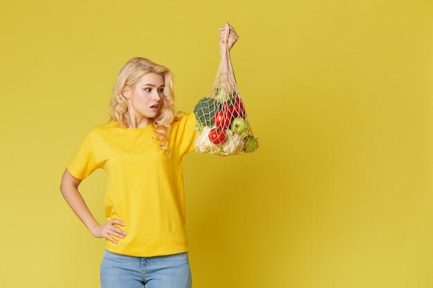De verraste vrouw houdt een koordzakhoogtepunt van organische groenten op gele muur.