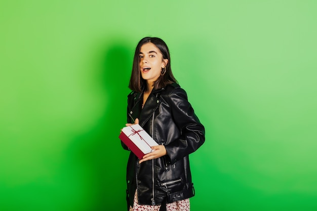 De verraste vrouw ontving gift en bekijkt camera over groene achtergrond