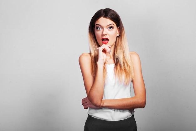 De verraste vrouw toont uw product met haar hand op grijze muur