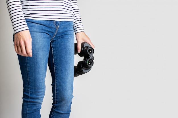 De verrekijkers van de vrouwenholding op een grijze achtergrond