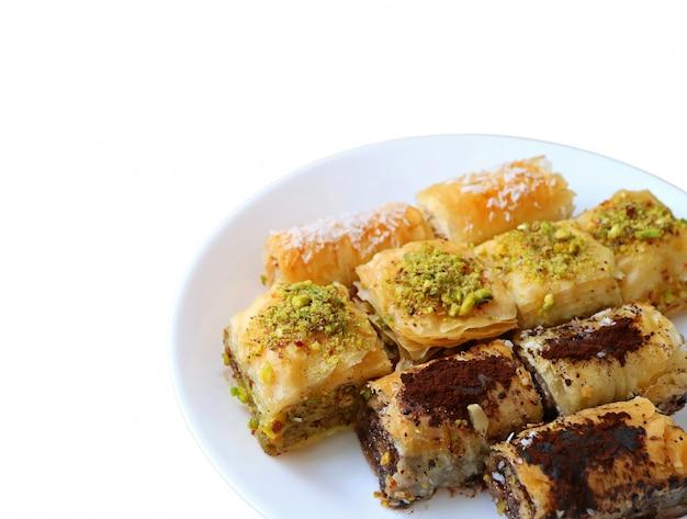 De verscheidenheid van mouthwatering baklava-gebakjes diende op witte die plaat op witte achtergrond wordt geïsoleerd