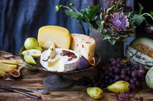 De verschillende kaas, vers fruit en tuinbloemen op oude houten lijst en blauwe achtergrond