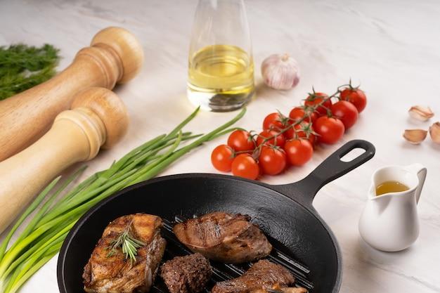 De verschillende soorten gebakken biefstuk in koekenpan close-up bekijk de verschillende soorten gebakken vlees groenten kruiden kruiden olie tomaat knoflook peper zout marmeren achtergrond hoge kwaliteit foto