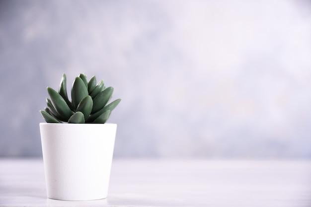 De verschillende vorm van kunstbloemengras in een pot op houten lijst dichte omhooggaand