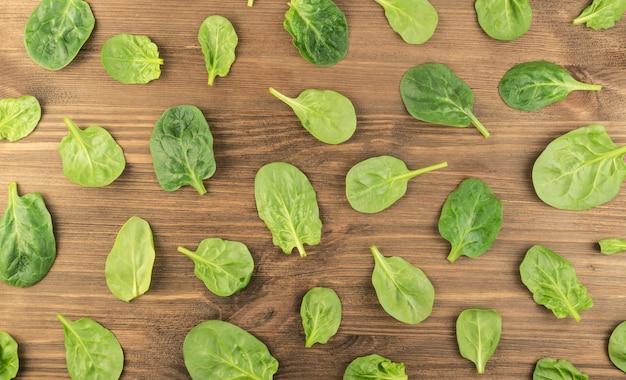 De verse bladeren van de babyspinazie op een houten lijst