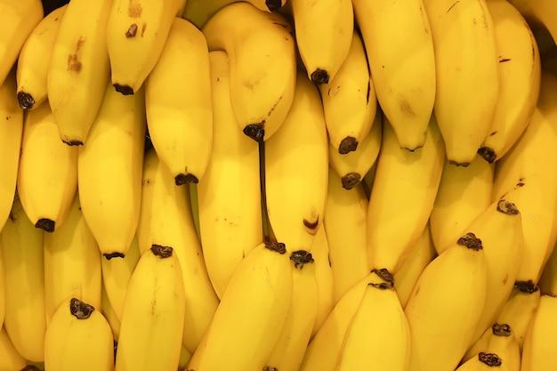 De verse gele natuurlijke achtergrond van bananendruiven