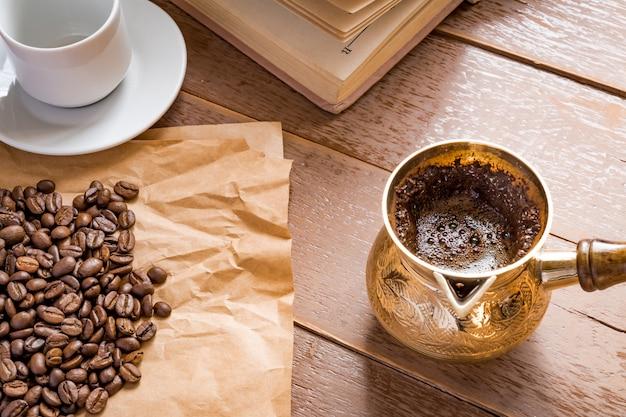 De verse geroosterde koffiebonen in cezve (traditionele turkse koffiepot) opende boek en kop op houten lijst.