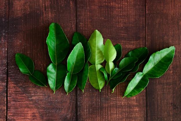 De verse groene bladeren van de kaffirkalk op houten bureau, het voedsel van azië