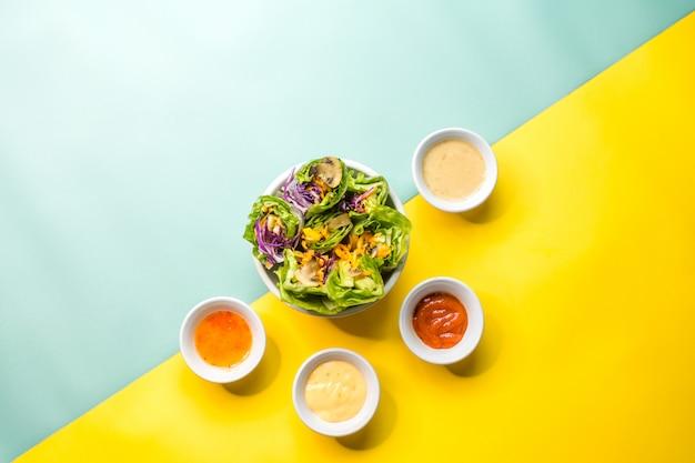 De verse groentesalade omgeven door zijn dressing op blauw en geel
