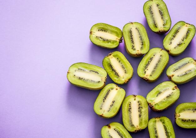De verse helften van kiwi op een purpere achtergrond