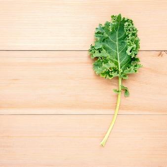 De verse organische boerenkool verlaat vlakke bladeren op een houten lijst met exemplaarruimte.