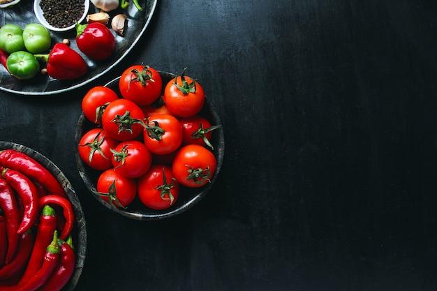 De verse organische rode tomaten in zwarte plaat, sluiten omhoog, gezond concept, hoogste mening