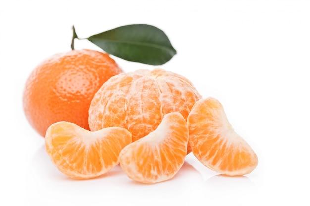 De verse organische vruchten van mandarinsmandarijnen met bladeren met de gepelde helften op witte achtergrond