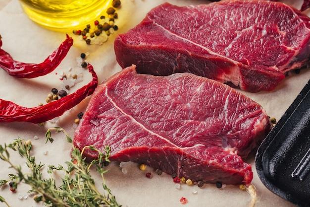 De verse ruwe plakken van het rundvleesvleeslapje vlees met kruiden en olijfolie klaar voor het koken