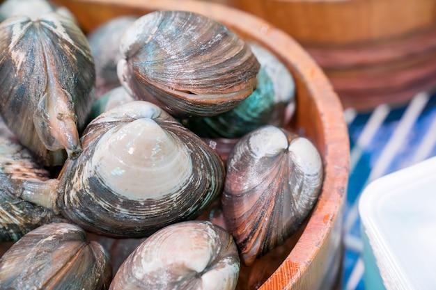 De verse schelpdieren op de vismarkt in een houten cirkeldoos klaar om te verkopen voor voedsel in japan.