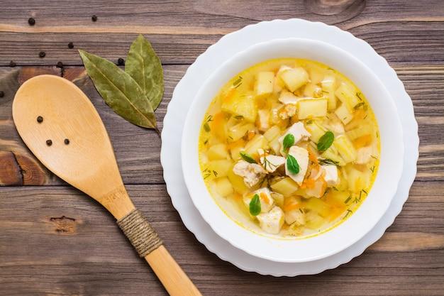 De verse soep van de kippenbouillon met aardappels en kruiden in een witte kom en houten lepel op een houten lijst. bovenaanzicht