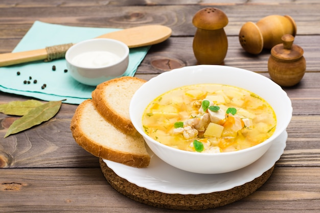 De verse soep van de kippenbouillon met aardappels en kruiden in een witte kom op een houten lijst