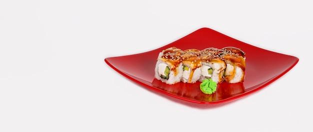 De verse sushi rolt van paling met sauskomkommer en de kaas van philadelphia op een rode plaat isoleren op een wit vlak